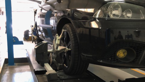 Mechanic checking a vehicles wheels - Wheel Alignment Heanor